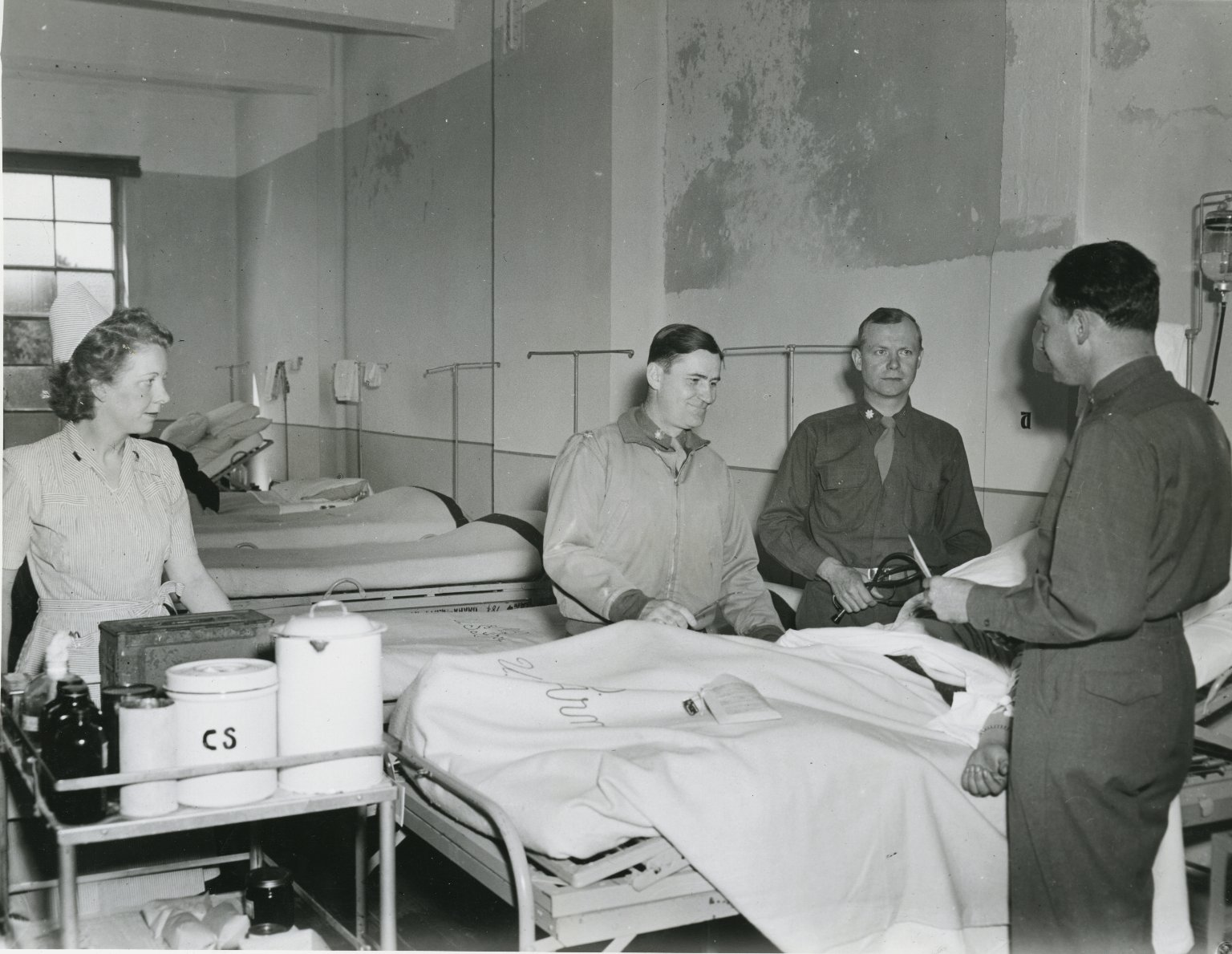 Doctors and Nurse Checking on Patient in Hospital Ward